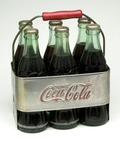 "1950's Coca-Cola aluminum six pack carrier, complete with bottles.  Embossed with the classic logo: ""Drink Coca-Cola"" on both sides. Central divider serves as a guide to keep the six bottles in place. Bottles remain filled with the beverage."