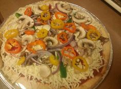 Store bought cheese pizza turned gourmet with sliced onions, peppers, mushrooms.