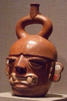 A Moche ceramic vessel from Pre-Columbian Peru with a traditional, straight stirrup-spout.  This face is often interpreted as belonging to a feline or fanged deity.  The bowl haircut and ear ornamentation are atypical for most of Moche art.  It could be priest or figure from another, neighboring culture. /NSC