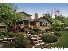 LOVE those stone steps and rock edge and retaining wall with the yard curving around.. the house isn't bad either, I also love river rock facing.. :)
