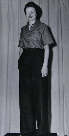 Sk3C Sharlene Osler models the new uniform, consisting of dungarees slacks and chambray shirt, which will replace the present aviation coverall worn by members of the Women's Reserve engaged in work requiring protective covering. The slacks are Navy blue denim with pockets on each side. The cotton chambray shirt is a lighter blue, with short sleeves and one patch pocket. The wrap-around turban is of Navy blue material ~