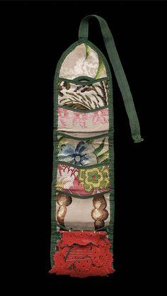 Sewing case, late 18th century. A sewing case, long and narrow in shape, designed to be rolled up and tied, outside embroidered with polychrome silks in rococo stitch, design of assorted small squares, inside a series of brocade pockets designed to contain sewing equipment, at bottom a needle book of five leaves of red wool with pinked edges and cut out design, edges bound with green silk tape, tie of same tape.