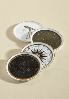 Night Sky Delights Coaster Set | Mod Retro Vintage Kitchen | ModCloth.com  Bring the ethereal serenity of star gazing into your home with these porcelain coasters by Chronicle Books! Black and metallic gold accents create constellations, compasses, and telescopic patterns atop this ivory set, indulging your explorative side from the comfort of your tabletop.