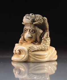 """Japanese carved netsuke of a Kappa, Japanese river sprite, emerging from its watery home. Head, shoulders and arms are visible above a breaking wave base. Intricate detailed etching and staining. Beaked mouth and shoulder length hair frame a head perched on scaled arms. The Sara has been concealed by a toad seated on the top of the Kappa's head, hind legs braced against its mounts shoulders, inlaid eyes. Signed Tomomasa. Size: 1.5"""" x 1.5""""."""