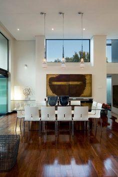 parquet en bois, chaises blanches et table en verre