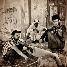 A group of young Bedouin men, reclining on their haunches, surrounded by Arabic graffiti