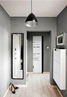 Przesuwane drzwi do łazienki sprawdzają się w wąskim korytarzu. Zrobiono je z płyty OSB oklejonej wydrukiem cytatu z Oscara Wilde'a.