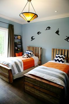 "Rad snowboard decal, chevron pillows, splash of orange, unique pallet bedframes, the whole setup screams ""I'm an epic decorator, and the people who use this room love me."""
