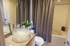 We knew the bathroom would be nice. The same granite in the kitchen is atop the vanity, which has a glass vessel sink. A simple gray shower curtain keeps the space neutral and calm.
