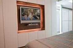 O armário, com portas sem puxadores, parece um grande painel para TV, garantindo bastante espaço para acomodar roupas sem impactar no resultado estético. - Revista Sua Casa