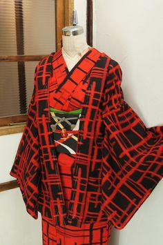 赤と黒のモダンなバイカラーで織り出されたモダンアートのような揺らぎのあるチェックデザインがスタイリッシュなウールのアンサンブル(着物と羽織のセット)です。