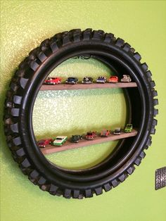 Repurpose an old dirt bike tire into a shelf. Hung on the wall with a towel hook. Just push in wood planks for shelving. Perfect for a boys room! Easy DIY.