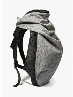 COTECIEL Nile Basalt Backpack | oki-ni: Crafted from mixed fabrics and textured leather, the bag draws on the texture Basalt igneous rock to give it a unique appearance. It also features a folding hood in the top pocket to protect the wearer from the rain.