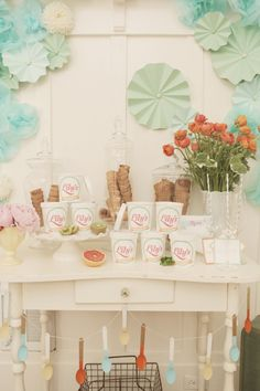 beautiful set-up with paper flowers + garland made of paint-dipped wooden spoons