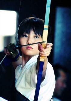 """Bir Japon kız """"atma sanatı Kyudo"""" tarzında oku çekerken."""