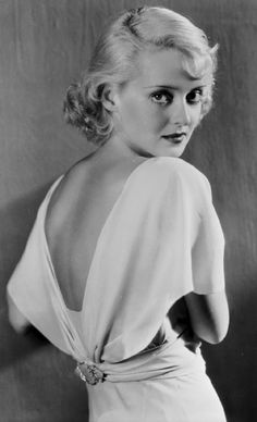 1930's Betty Davis. white low cut back with a looser sleeve, adhered with an embellished waist belt and a straight cut, full length (to the ankle) skirt. this is paired with shingle curls