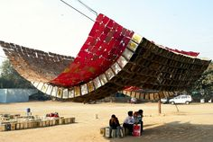 The shade structure above, by architect Sanjeev Shakar, is shaped in an upside-down arch made of 945 cooking-oil cans