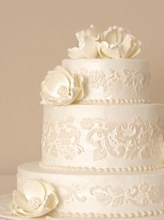 This three-tiered wedding cake is iced white butter cream with a stenciled champagne floral print, pearl luster and large magnolias. It is a white almond wedding cake with buttercream filling. Haydel's Bakery, haydelbakery.com