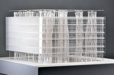 "A model of the Sendai Mediatheque.  ""It is laser cut acrylic with hand threaded neoprene cord for the columns. It is lit by led lights from below in blue and cool white."""