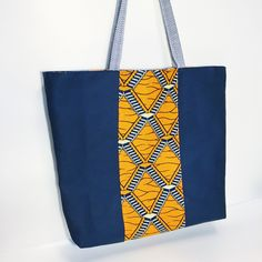 Fully lined canvas tote bag with blue and white striped shoulder straps and orange and blue printed stripe and interior! Love the use of African print and nautical color scheme together - this bag is great on the go!