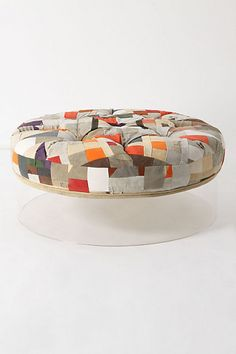Patchwork upholstered ottoman on a lucite base. It looks like the cushion is positively levitating! Bohemian and mod at the same time!