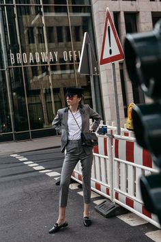 Fashion blogger Beatrice Gutu wearing The Kooples suit with black leather slippers and baker boy hat in New York inspired street editorial