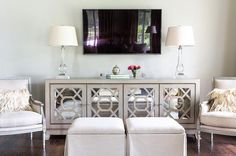 Chic living room features a pair of gray French chairs and oatmeal linen skirted ottomans placed in front of a gray mirrored cabinet fitted with mirrored trellis doors topped with crystal lamps placed under a flat panel tv. Mirrored sideboard buffet door detail