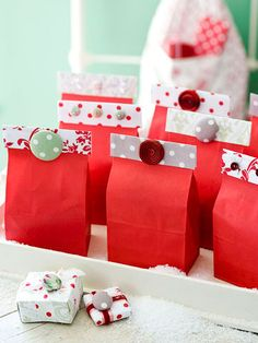 christmas favors: wrap up party favors or small Christmas gifts in red bags embellished with a band of fabric. Cut strips of fabric long enough to fit around the bag opening. Fold the top of the bag over on itself and wrap a fabric strip around it, using double-sided tape to secure. Finish the wrapping with a decorative sticker or button.