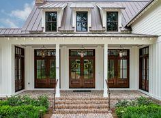 A front entryway times three! Three peaked windows, three doors and three French Quarter Lanterns on Yokes.