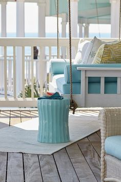 Relax and unwind on a porch with a white swing fitted with Caribbean blue cushions beside a blue stool accent table. Relax and unwind on a porch with a white swing fitted with Caribbean blue cushions beside a blue stool accent table. Cottage Porch, Coastal Cottage, Coastal Living, Chic Beach House, Dream Beach Houses, White Porch, Summer Porch, Outdoor Furniture Sets, Outdoor Decor
