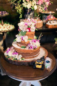 Bolo de casamento naked com três andares, recheio de doce de leite, decorado com flores naturais e personagens como topo de bolo