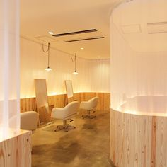 Japanese architects Maker have completed a hair salon featuring gauze partitions and booths in untreated wood.