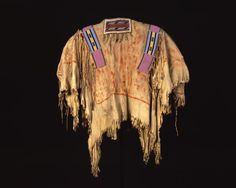 C 1885  Elk hide shirt; painted front to lower section and up sleeves; red ring at end of sleeve; multitude of hide croppings sewed together with dark brown thread; beaded strips in turquoise green, red white hearts, pink, light blue, dark blue, white and yellow; front piece beaded with dark blue and light blue framed in white beads, 7 tassles with hair (neck piece); beaded strips down sleeves in dark glass green, pink, red white hearts, dark blue, yellow, lime green and white; fringes…