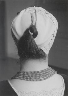 Demonstratie van het 'kapzetten' van de 'lange muts' te Westkapelle. 1956 Het samengebonden haar wordt met een bandje bijeen gebonden en naar boven geslagen. Vervolgens wordt de haarstreng met de uiteinden van het bandje aan het achterbolletje van de ondermuts gespeld. De loshangende uiteinden van de haarstreng worden tussen de haarstreng en de ondermuts weggewerkt. #Zeeland #Walcheren