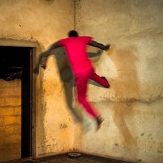Dominic Nahr. MALI. Bamako. 2016. A dancer jumps up a wall during a contemporary dance routine in Kettly Noel's dance studio called Donko Seko.