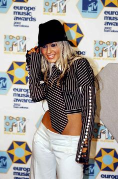 Christina Aguilera's menswear top, black clip-ins, and fedora.