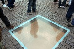 "Book Burning Memorial - In the center of Bebelplatz, Berlin, a glass window showing rows and rows of empty bookshelves. The memorial commemorates the night in 1933 when 20,000 ""anti-German"" books were burned. There's a plaque nearby that says ""Where they burn books, they will also burn humans in the end."""