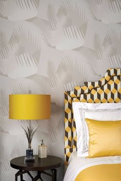 Grey tropical design wallpaper that provides some lucidity to the bright yellow colors of the textiles and table lamp.