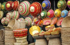 An Indian woman waits for customers at her roadside stall selling cane baskets in Hyderabad, India