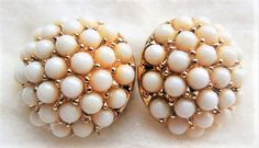 Vintage Coro White Beaded, Gold Tone, Clip On Earrings, Vintage and Signed White beads cluster in gold tone settings to make a stand out pair of clip on earrings. I see this for wedding earrings for guest or mother of the bride. Coro quality and affordability always. Signed Coro on the back clips. Lovely little white beads, on bright gold setting, The backs have wear but work fine. Vintage and worn and a lovely set.