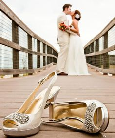 "Kick off your shoes for this memorable shot!    Why You Love It: ""Very cute!"" —Something Borrowed Bride  ""I have seen a los of photos high lighting the wedding dress alone. I like the concept of this photo better, the shoes, beach, and the kiss. Very well done!"" —Cyhallatlanta    Photo Credit: Clear Skies Photography"