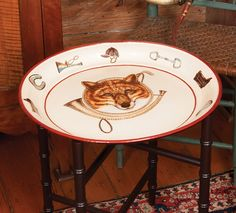 """Fox Metal Tole Tray. Hand-painted tray with a fox mark and hunting horn in center. Equestrians symbols arranged on the border. Trimmed in dark red. An impressive accent for the fox loving home. 20"""" tray is made of heavy gauge iron, hand-painted and varnished. This multi functional fox tray can be used as a tray, table, display on a hutch or hang on wall with plate hangers."""