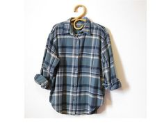 This 90s vintage blue flannel shirt has a button down front and 1 chest pocket. Nice style for guys or gals!  Material: cotton Colors; steel blue, navy, beige  Please refer to measurements for best fit! Measurements: measured flat Armpit to armpit 22 Body length 25 Shoulder to shoulder 18 Sleeve length - from shoulder seam 20 (sleeve may be a bit short for men, however ok when wearing with sleeves rolled up))  Vintage condition: good Delivered clean and ready to wear ***Machine wash in cold…
