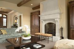 Great stone fireplace, niches on each side housed with armoires, benches, ottoman, beamed ceiling.
