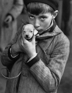 """Andre Kertesz - Boy Holding Puppy, 1928 * Extracts from Roland Barthes' Camera Lucida: """"He is looking at nothing; he reta. Andre Kertesz, Henri Cartier Bresson, Robert Doisneau, Andy Warhol, Great Photos, Old Photos, Claudio Edinger, Foto Face, Street Photography"""
