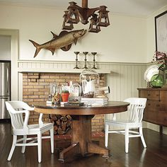 So much dark oak  table and sideboard. Want a modern contrast... solution was to have the chairs commercially sprayed in a light driftwood color. The light-colored wainscot adds additional contrast to the bungalow's dark wood floors.