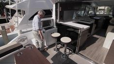 Cruisers Yachts 54 Cantius: The cockpit has a large table with a wraparound settee, two stools at the bar with a grill alongside. Here the galley window is down, and the doors are opened to remove any separation of the inside and the outside.