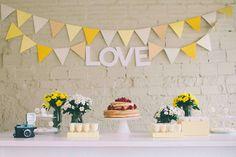 Mesa de noivado simples, e fofa. Usando bandeirinhas de cartolina (ou qualquer outro papel) e arranjo de flores.