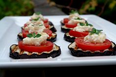 Grilled eggplant slices topped with tomato slices, garlicky parmesan sauce and fresh herbs.