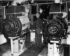 North Star Drive-In - Photo of projectionist John Templeton posing with two behemoth DP70 projectors in the North Star Drive-In booth.  Two DP70. 1600 cars. Screen 135 x 60 ft. Jet arc lamps. One DP70 moved to the Cooper 5 Theatre (Aurora) and the other on was moved to the Cooper 6.
